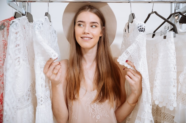 Uśmiechający się piękna młoda kobieta w kapeluszu stojący w sklepie odzieżowym