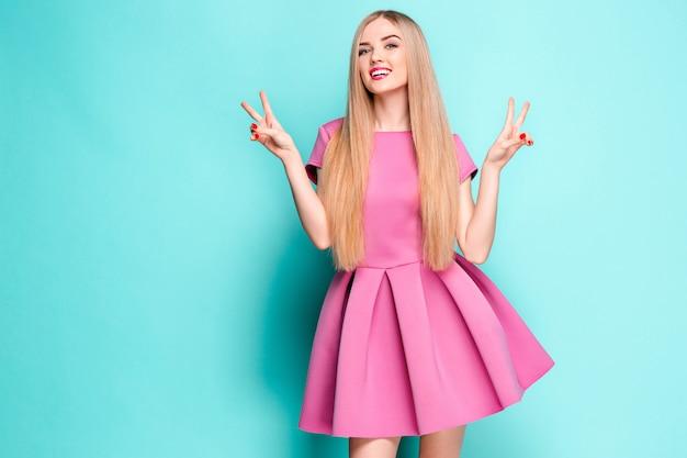 Uśmiechający się piękna młoda kobieta w różowej mini sukience pozowanie