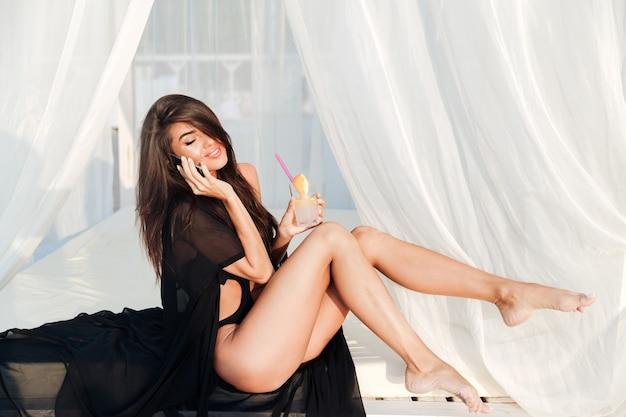 Uśmiechający się piękna szczęśliwa kobieta rozmawia przez telefon i pije koktajl na plaży