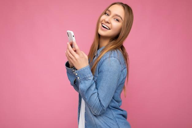 Uśmiechający się piękny pozytywny młoda blondynka na sobie dorywczo niebieską koszulę jean na białym tle nad różowym tle
