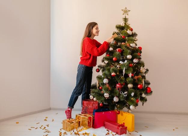 Uśmiechający się podekscytowany ładna kobieta w czerwonym swetrze stojącym w domu dekorowanie choinki otoczonej prezentami i pudełkami na prezenty