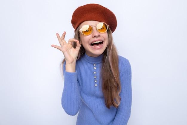 Uśmiechający się pokazując w porządku gest piękna mała dziewczynka w okularach z kapeluszem na białym tle na białej ścianie