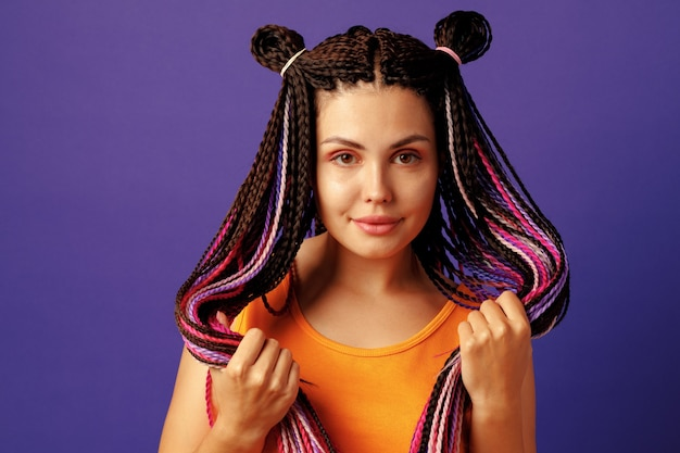 Uśmiechający się pozytywna młoda kobieta z kolorowymi afrykańskimi warkoczami na fioletowo