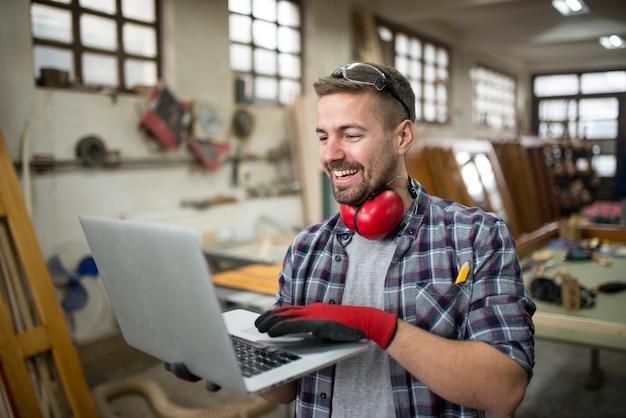 Uśmiechający się pozytywny stolarz za pomocą laptopa w warsztatach stolarskich, dzieląc się pomysłami