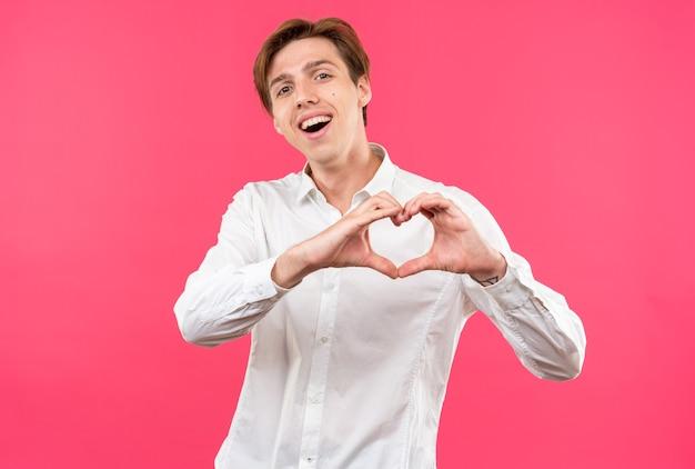 Uśmiechający się przechylony młody przystojny facet ubrany w białą koszulę pokazujący gest serca na różowej ścianie
