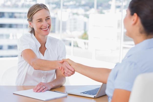 Uśmiechający się przesłuchujący drżenie ręki wnioskodawcy