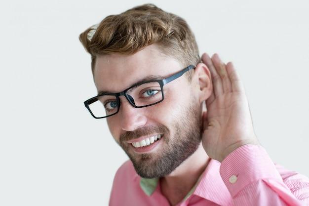 Uśmiechający się przystojny mężczyzna trzyma rękę w pobliżu ucha