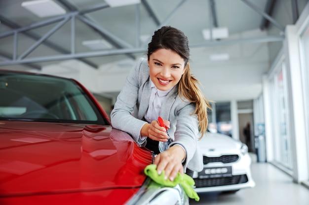 Uśmiechający się schludny żeński sprzedawca samochodów pociera samochód detergentem i szmatką. wszystko musi być błyszczące i czyste.