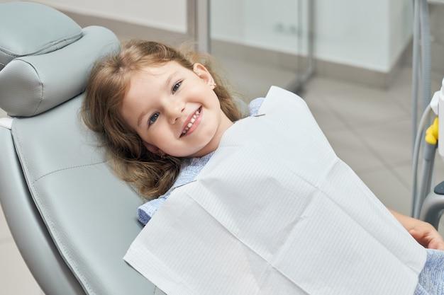 Uśmiechający się słodkie, małe dziecko siedzi w fotelu dentystycznym.