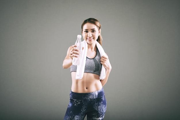 Uśmiechający się sprawny azji kobieta w odzieży sportowej, z ręcznikiem na ramionach, wyciągając butelkę wody