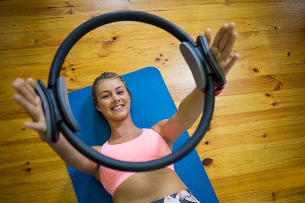 Uśmiechający się sprawny kobieta ćwiczenia z pierścieniem pilates na macie