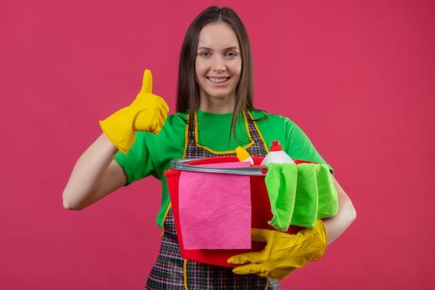 Uśmiechający się sprzątaczka młoda dziewczyna ubrana w mundur w rękawiczkach trzymając narzędzia do czyszczenia jej kciuk na na białym tle różowym tle