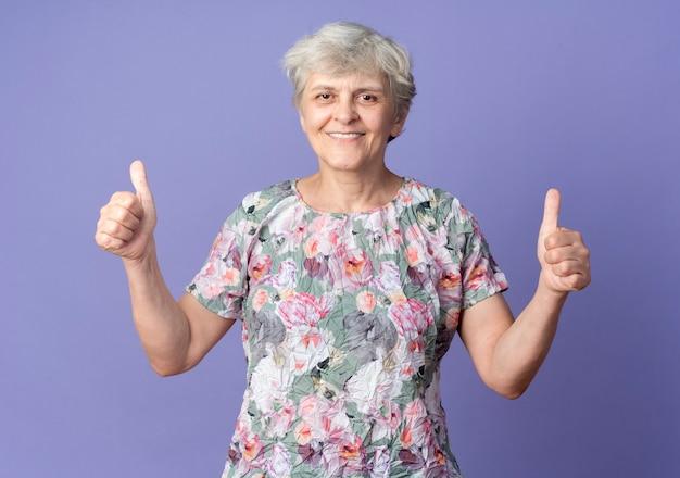Uśmiechający się starsza kobieta kciuki dwiema rękami na białym tle na fioletowej ścianie