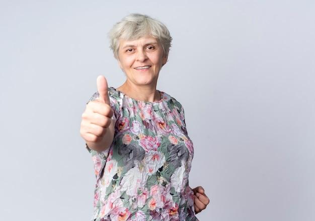 Uśmiechający się starsza kobieta kciuki na białym tle na białej ścianie