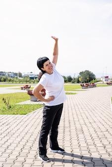 Uśmiechający się starszy kobieta rozgrzewa się, rozciągający się na świeżym powietrzu w parku