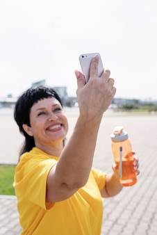 Uśmiechający się starszy sportsmenka robi selfie na świeżym powietrzu w parku