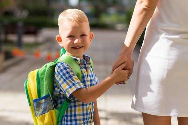 Uśmiechający się uczeń ręka matki gospodarstwa