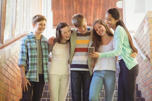 Uśmiechający się uczniowie stojący na schodach za pomocą telefonu komórkowego