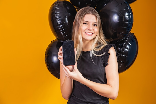 Uśmiechający się uroczy młoda kobieta z telefonem komórkowym z pustym pustym ekranem na żółtym tle z portretem studio balonów. wyprzedaż w czarny piątek