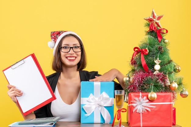 Uśmiechający się uroczy pani w garniturze z santa claus hat i okularami, trzymając dokumenty wskazujące prezent w biurze na żółtym na białym tle