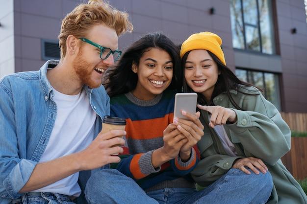 Uśmiechający się wielorasowi przyjaciele za pomocą telefonu komórkowego, oglądając zakupy wideo online