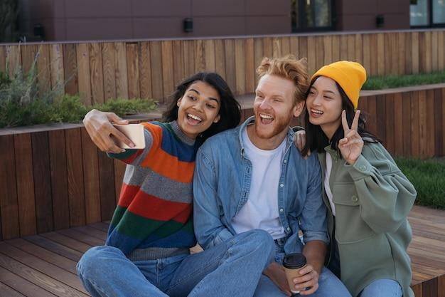 Uśmiechający się wielorasowi przyjaciele za pomocą telefonu komórkowego robienia selfie, zabawy na świeżym powietrzu