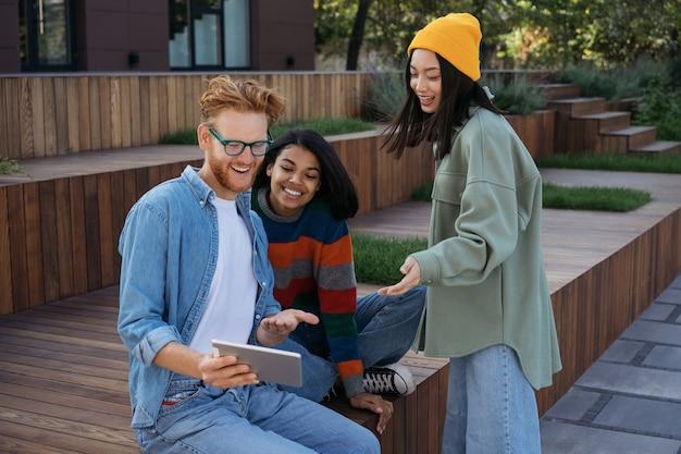 Uśmiechający się wielorasowi studenci za pomocą cyfrowego tabletu, studiując razem
