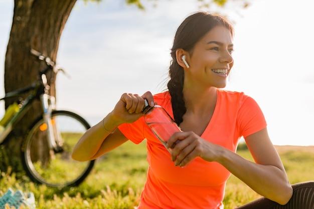 Uśmiechający się wody pitnej piękna kobieta w butelce uprawiania sportów rano w parku
