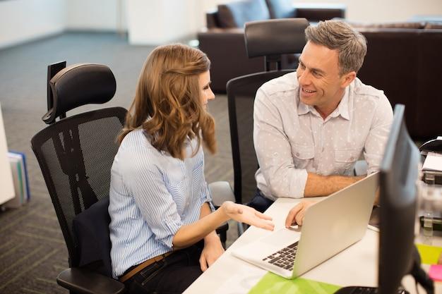 Uśmiechający się współpracownicy, omawiając podczas wspólnej pracy