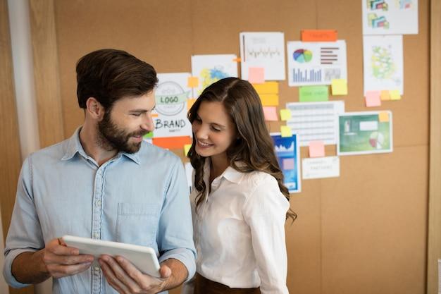 Uśmiechający się współpracownicy pracujący na cyfrowym tablecie w biurze