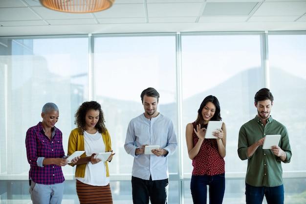 Uśmiechający się zespół kreatywny biznes za pomocą cyfrowego tabletu w biurze