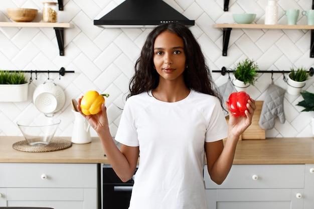 Uśmiechana oliwkowa kobieta o luźnych włosach trzyma czerwoną i żółtą paprykę w dłoniach w pobliżu biurka kuchennego na nowoczesnej białej kuchni ubrana w białą koszulkę