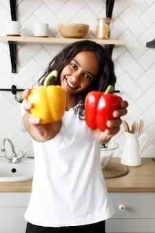 Uśmiechana oliwkowa kobieta ubrana w białą koszulkę, o ładnej buzi i luźnych włosach pokazuje żółtą i czerwoną paprykę