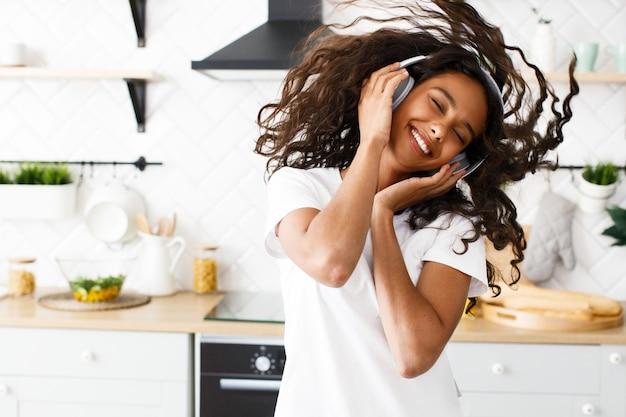 Uśmiechana oliwkowa kobieta z kręconymi włosami w dużych bezprzewodowych słuchawkach szczęśliwie tańczy z zamkniętymi oczami w nowoczesnej kuchni