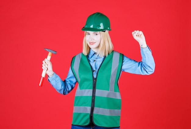 Uśmiechnęła się pracownica trzymaj młotek i pokazując jej pięść odizolowaną na czerwono