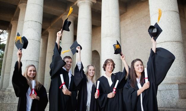 Uśmiechnięci absolwenci trzyma ich kapelusze przed uniwersytetem