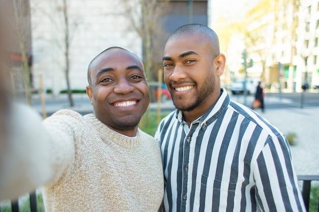 Uśmiechnięci amerykan afrykańskiego pochodzenia przyjaciele bierze selfie