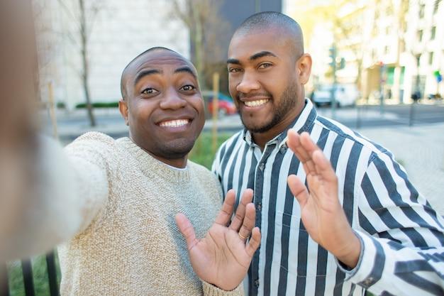 Uśmiechnięci amerykan afrykańskiego pochodzenia przyjaciele macha podczas gdy brać selfie