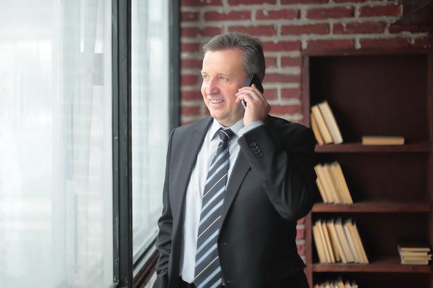Uśmiechnięci biznesmeni rozmawiający przez telefon.zdjęcie z miejscem na kopię