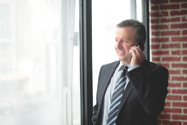 Uśmiechnięci biznesmeni rozmawiający przez telefon