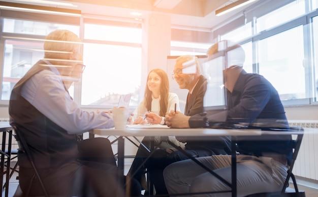 Uśmiechnięci biznesmeni zespalają się obsiadanie wokoło stołu w spotkaniu