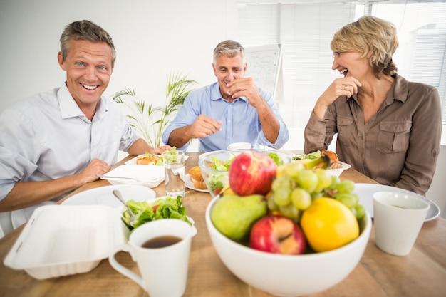 Uśmiechnięci biznesowi koledzy ma lunch wpólnie