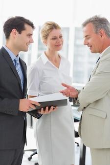 Uśmiechnięci biznesowi koledzy opowiada wpólnie
