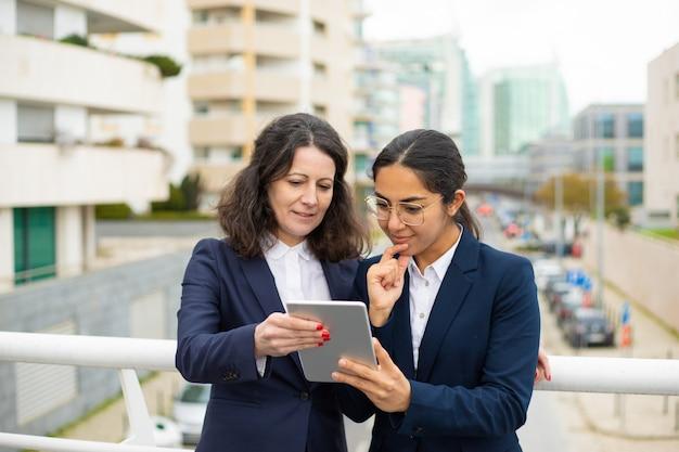 Uśmiechnięci bizneswomany używa pastylka komputer osobistego