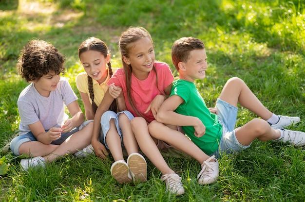 Uśmiechnięci chłopcy i dziewczęta siedzący na zielonym trawniku