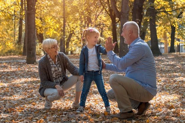Uśmiechnięci dziadkowie i wnuki bawią się razem w jesiennym parku