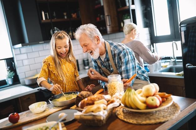 Uśmiechnięci dziadkowie jedzą śniadanie z wnuczką