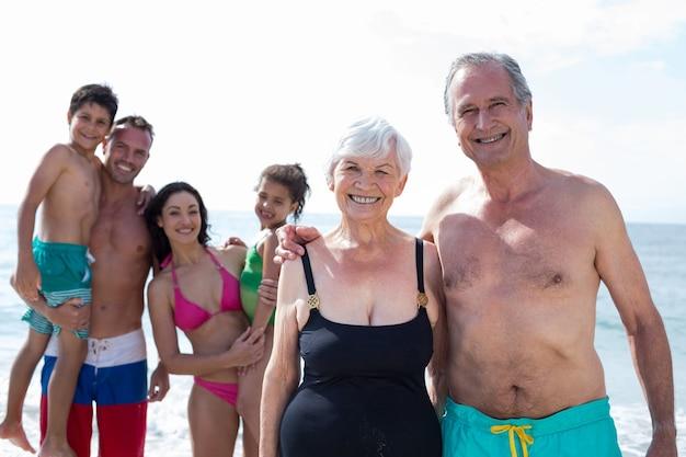 Uśmiechnięci dziadkowie z rodziną na plaży