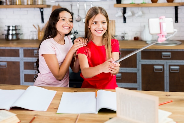 Uśmiechnięci dzieci siedzi przy biurkiem i bierze selfie przy kuchnią