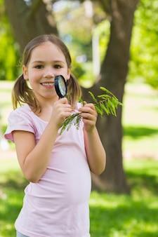 Uśmiechnięci dziewczyny mienia liście i powiększać - szkło przy parkiem